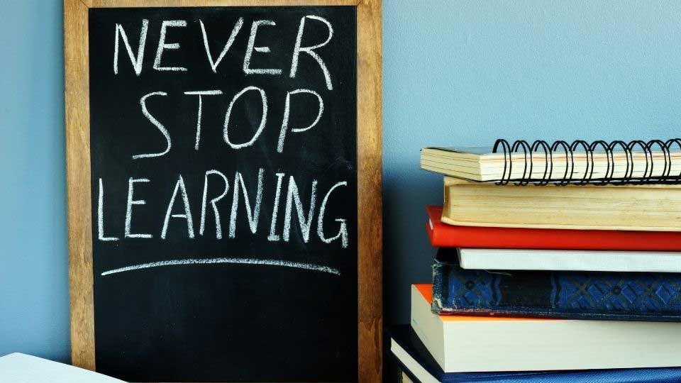 Never stop learning message next to books