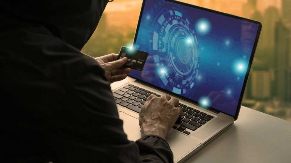 Person holding a card in front of a laptop